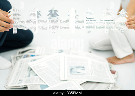 Two people holding tree shapes cut out of newspaper, cropped view - Stock Photo