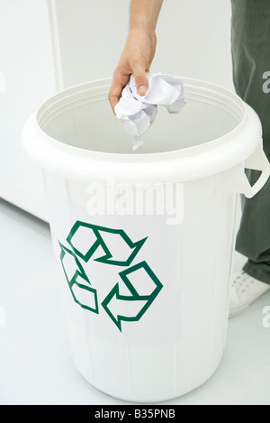 Man throwing crumpled paper in recycling bin, cropped view - Stock Photo