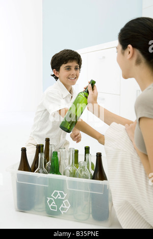 Young woman and boy placing glass bottles in recycling bin, smiling at each other - Stock Photo