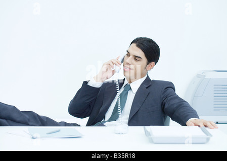Young businessman sitting with feet up at desk, talking on landline phone - Stock Photo