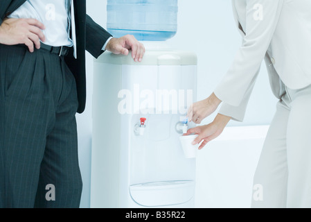Professional woman filling disposable cup with water from water cooler, male colleague standing nearby, cropped - Stock Photo