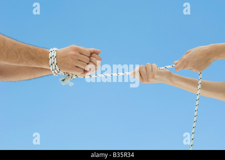 Male hands bound by rope, female hands pulling rope, cropped view - Stock Photo