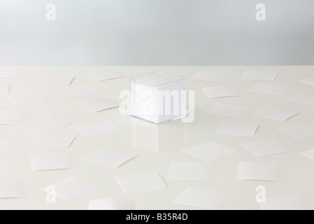 Scattered sheets of paper around a stack of paper in plastic container - Stock Photo