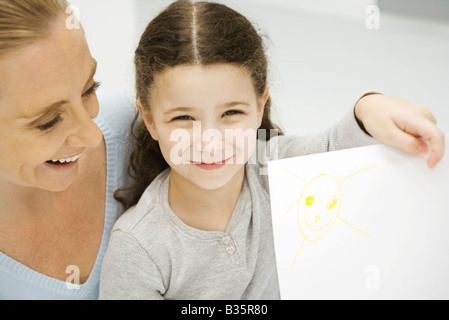 Girl holding up and showing drawing of the sun, mother smiling behind her daughter - Stock Photo
