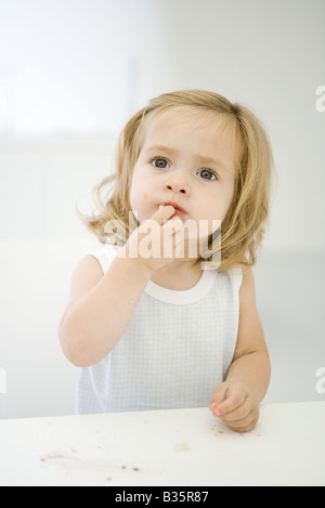 Little girl sitting at messy table, wiping a crumb off her lip - Stock Photo