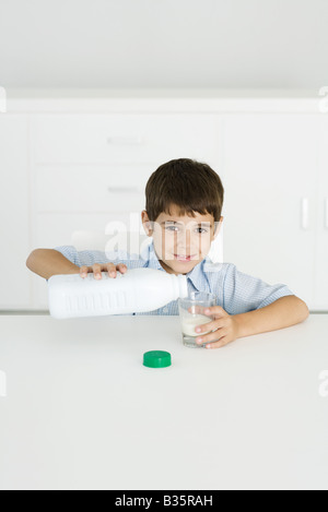 Boy pouring milk into empty glass, smiling at camera - Stock Photo