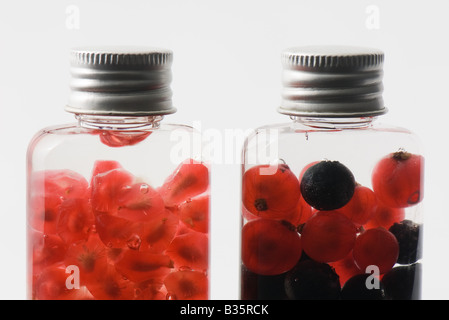 Bottles containing fresh berries and pomegranate seeds, close-up - Stock Photo