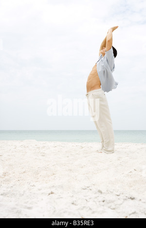 Man standing in sun salutation pose on beach, side view - Stock Photo