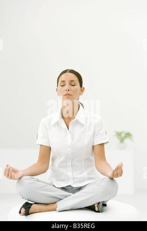Woman sitting cross-legged, meditating with eyes closed - Stock Photo