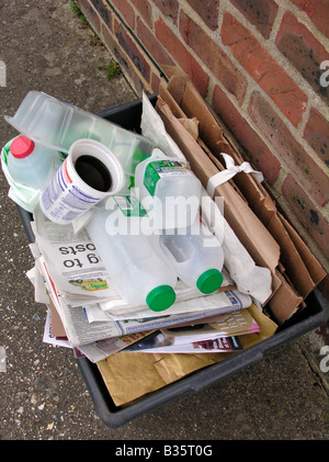 recycling bin filled with newspapers plastics for kerbside collection Worthing West Sussex - Stock Photo
