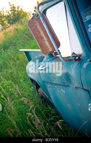 Abandoned rusty old truck in a field - Stock Photo