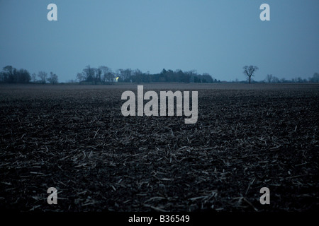RURAL MIDWESTERN FARMLAND WITH FARM BUILDINGS IN A DISTANCE AT NIGHT IN EARLY SPRING NORTHERN ILLINOIS USA - Stock Photo