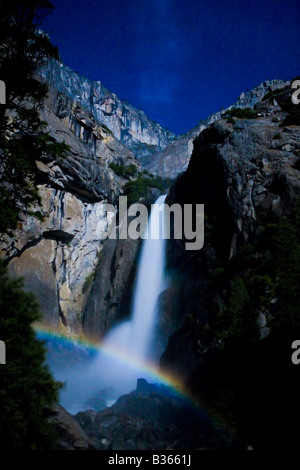 A lunar rainbow moonbow forms over the base of lower Yowemite Falls Yosemite National Park California USA - Stock Photo