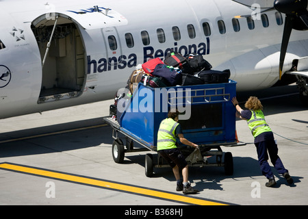 Lufthansa Regional Baggage handler moving luggage at airport air side British Airport Jersey Channel Islands - Stock Photo
