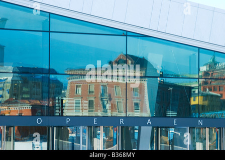 Detail of the new opera house in Oslo Norway with the older architecture of the city reflected in its glass facade - Stock Photo