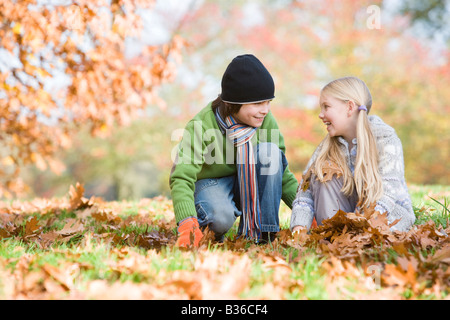 Two young children outdoors in park playing in leaves and smiling (selective focus) - Stock Photo