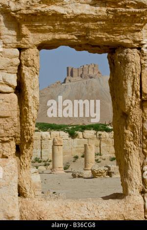 Arab Castle Qalaat Ibn Maan through the Roman Ruins of Palmyra in Syria - Stock Photo