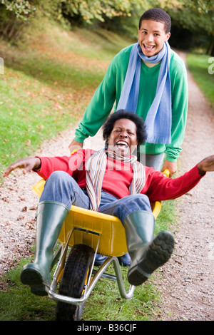 Young boy outdoors pushing mother in wheelbarrow and smiling (selective focus) - Stock Photo