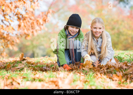Two young children outdoors at park playing in leaves and smiling (selective focus) - Stock Photo