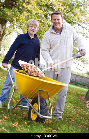 Man outdoors with young boy shoveling leaves into wheelbarrow and smiling (selective focus) - Stock Photo