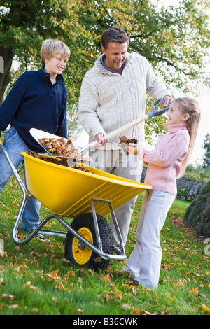 Father outdoors with two young children shoveling leaves into a wheelbarrow and smiling (selective focus) - Stock Photo