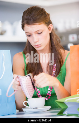 Young woman sitting at a table checking change purse - Stock Photo