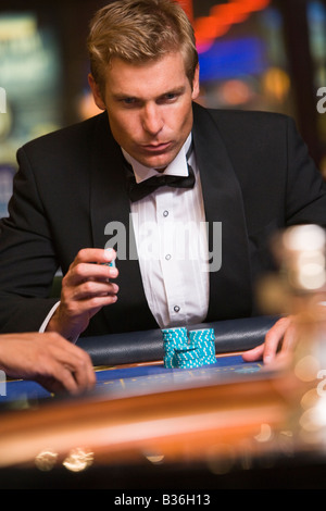 Man in casino playing roulette (selective focus) - Stock Photo
