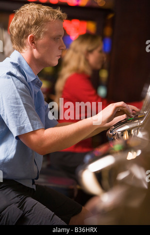 Man in casino playing slot machine with people in background (selective focus) - Stock Photo