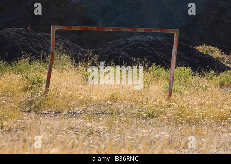 Old battered rusted football goalpost in uncared for field - Stock Photo