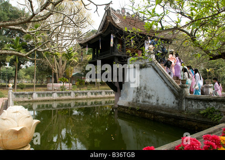 A crowd of Vietnamese woman dressed in traditional Ao Dai climb the steps of One pillar Pagoda in Hanoi Vietnam - Stock Photo