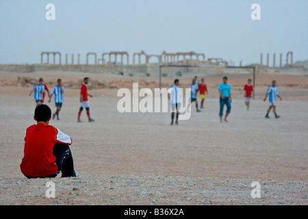 Syrian Boy Watching Football in front of the Roman Ruins of Palmyra in Syria - Stock Photo