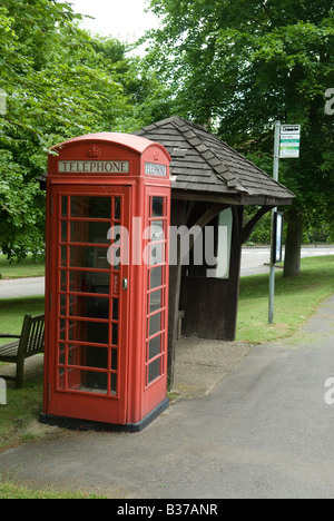 Red phone box next to Bus stop in village Buckinghamshire, UK - Stock Photo