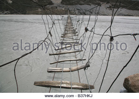 Footbridge over Hunza river, near Passu, northern Pakistan. - Stock Photo