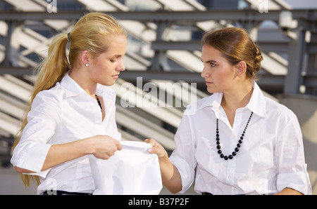 picture of two angry businesswomen fighting for contract - Stock Photo
