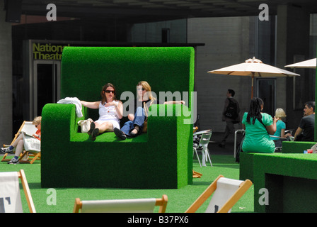 Women sitting on an over-sized green grass chair outside the National Theatre in London - Stock Photo