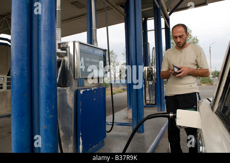Man filling his car with petrol at a filling station in Tbilisi capital of Republic of Georgia - Stock Photo