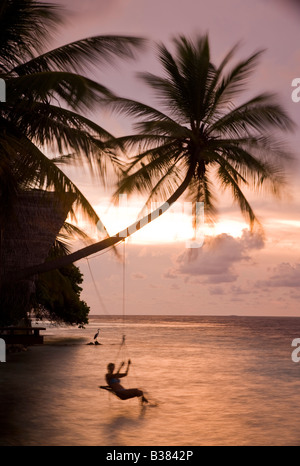 Girl swinging on rope swing at sunset on South Ari Atoll in Maldives near India - Stock Photo