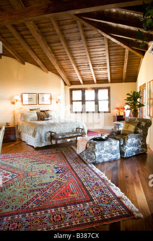 large master bedroom with vaulted ceilings and area rug