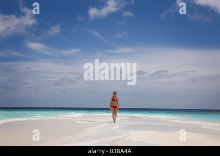 Young woman walking along deserted white sand beach surrounded by tropical waters in Maldives near India - Stock Photo