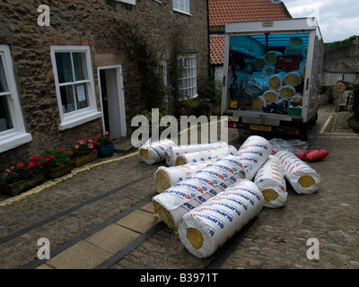 Unloading a van with rolls of loft insulation in a cobbled street in Richmond, North Yorkshire - Stock Photo