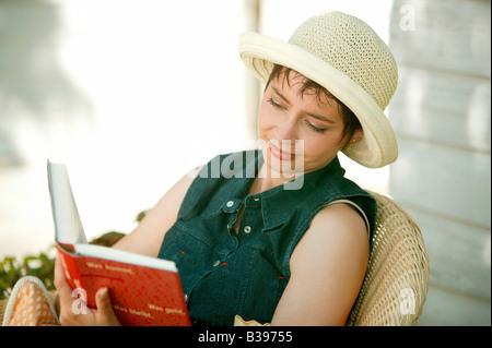 Frau liest ein Buch im Garten, Woman reads a book in the garden - Stock Photo