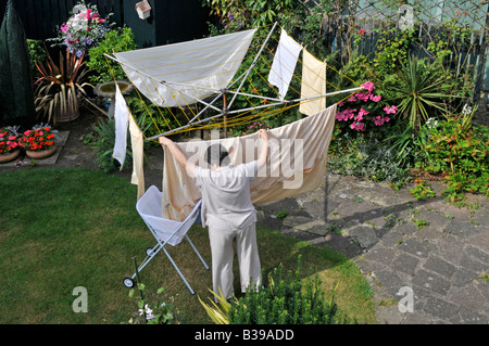Woman hanging out washing to dry on rotary clothes line in back garden - Stock Photo