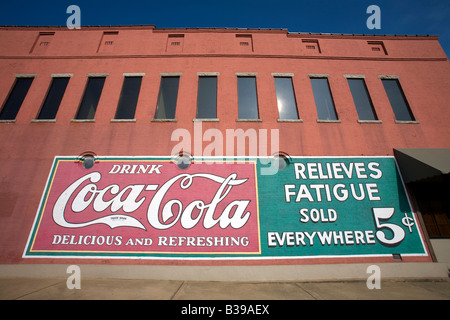 A vintage Coca Cola sign painted on the side of a building in downtown Rogers, Arkansas, U.S.A. - Stock Photo