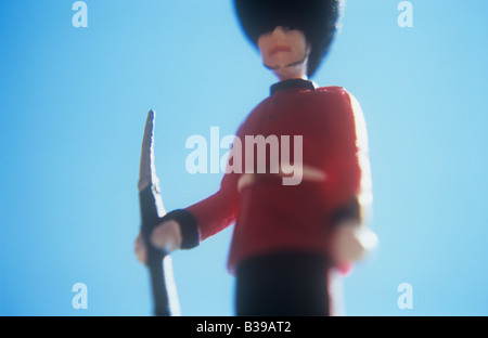 Detail from below of model of archetypal soldier or guardsman with bayonet rifle red jacket and black busby under - Stock Photo