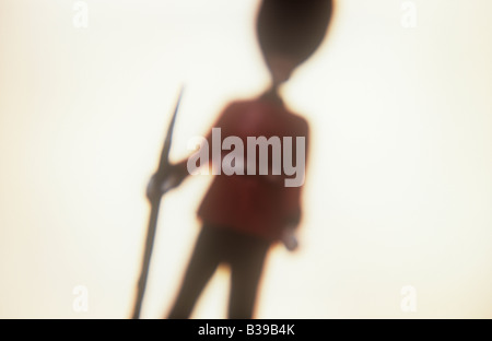 Impressionistic close up of model of archetypal soldier or guardsman with bayonet rifle jacket and busby against - Stock Photo
