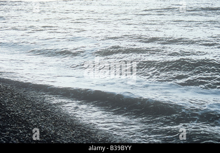 An uninviting silver grey sea with large swell breaking onto shore of smooth rounded gray pebbles - Stock Photo