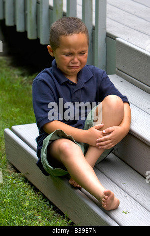 Young Latino boy outside sitting on a step holding his leg in pain - Stock Photo