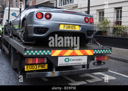 Illegally parked Ferrari being towed away - Central London - Stock Photo