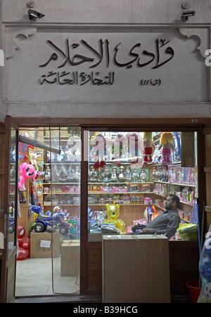 owner of toyshop resting on his chair in Deira Old Souk Bazar Besitzer ruht sich in seinem Kinderspielzeugladen - Stock Photo