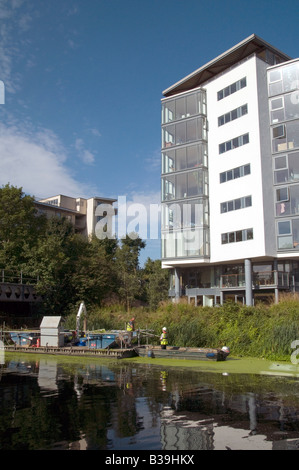 UK. Maintenance dredging team by new luxury flats on the Lea Canal near the Olympic Park, East London.Photo © Julio - Stock Photo
